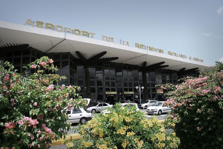 Budova letiska, pred ktorou stoja autá.jpg