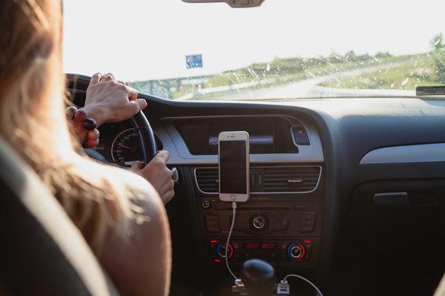 Žena s blond vlasmi šoféruje auto.jpg