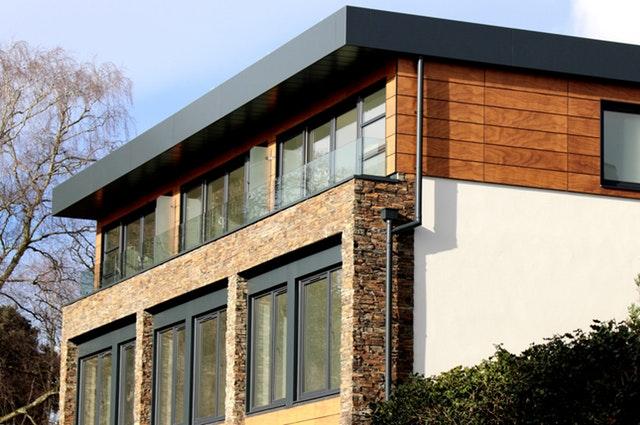 Dom s veľkými oknami a presklenou stenou na druhom poschodí.jpg