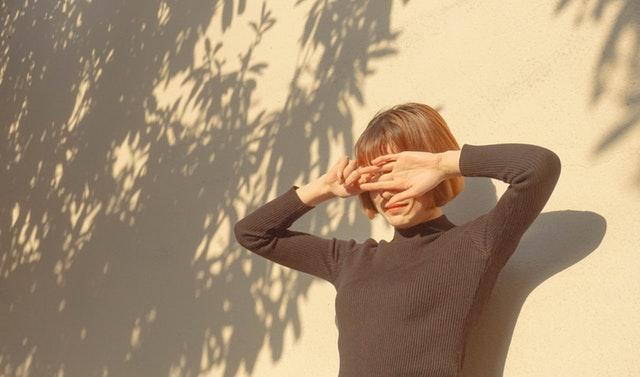 Žena stojí pri stene a zakrýva si oči pred slnkom.jpg