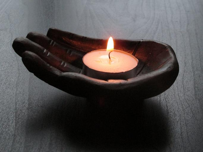 Umelá ruka, sviečka, symbol relaxu a masáže