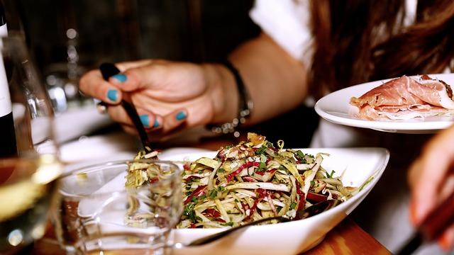 Žena obeduje a v ruke drží tanier so slaninou.jpg