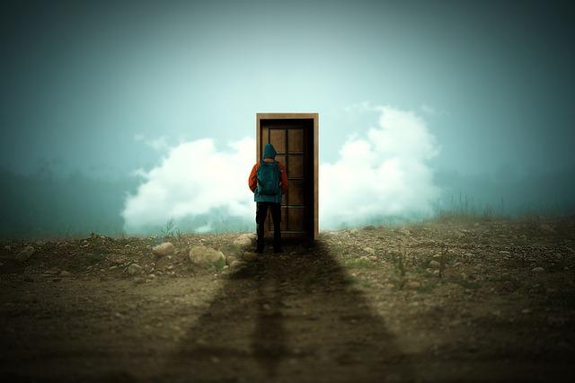 Muž s ruksakom a v bunde stojí pred dverami na lúke pri zamračenom nebi.jpg