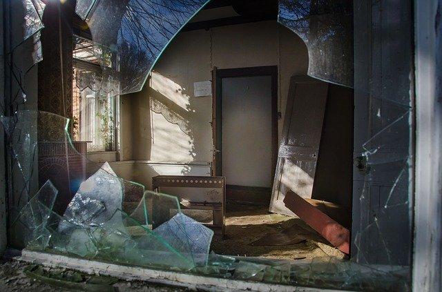 Pohľad cez rozbité okno do interiéru s rozhádzaným nábytkom.jpg