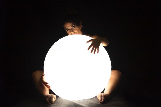 Nahá žena pred sebou drží veľkú svietiacu bielu guľu